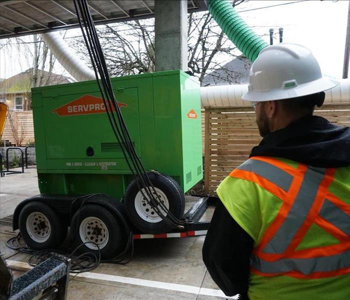 SERVPRO employee in PPE stands next to SERVPRO green generator