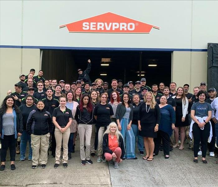 Servpro staff stand together in front of the warehouse